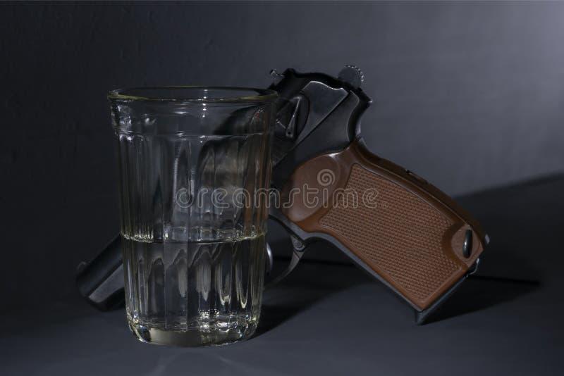 Vidrio con la vodka y un arma en el piso foto de archivo