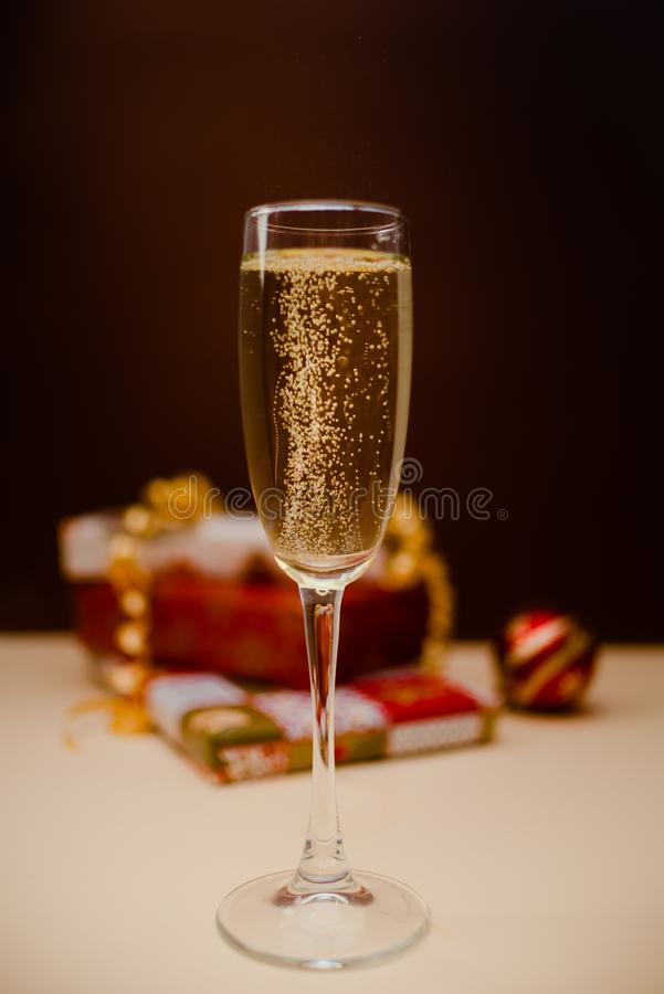 Vidrio con las burbujas Vidrio del shampagne de la Navidad con los presentes en el fondo imagen de archivo