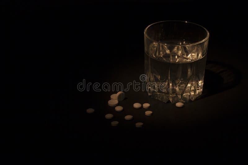 Vidrio con píldoras alrededor en la oscuridad foto de archivo