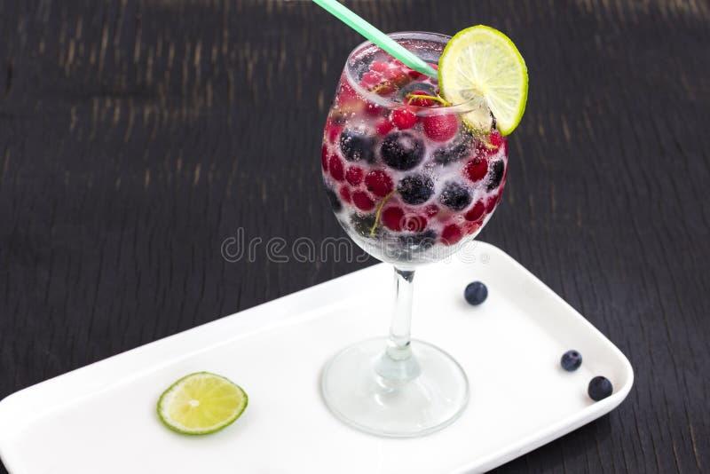 Vidrio con una bebida de enfriamiento de bayas y del hielo Vidrio de Misted Burbujas de aire sobre el vidrio de vidrio Fondo negr imagen de archivo libre de regalías