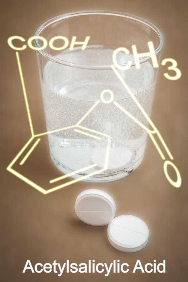 Vidrio de agua con el ácido acetilsalicílico fotografía de archivo