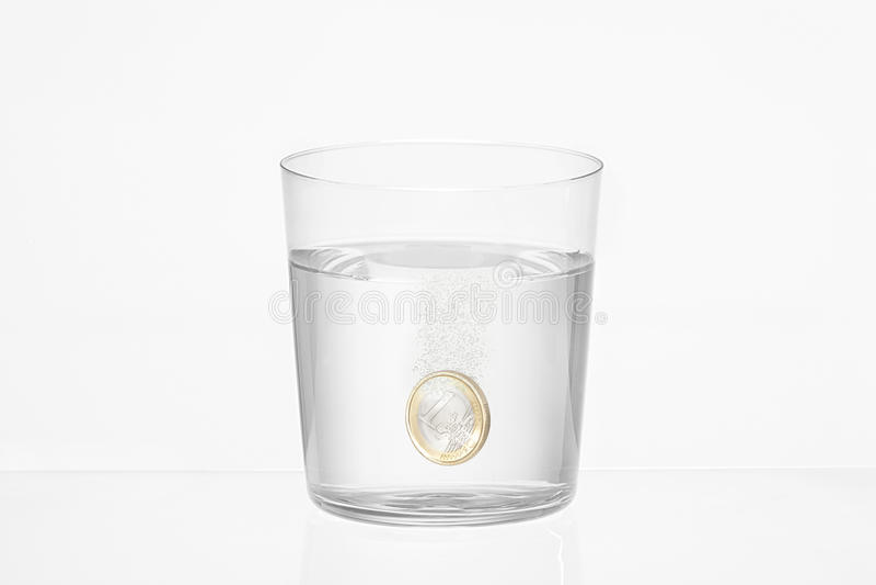 Vidrio de agua con una moneda euro adentro foto de archivo