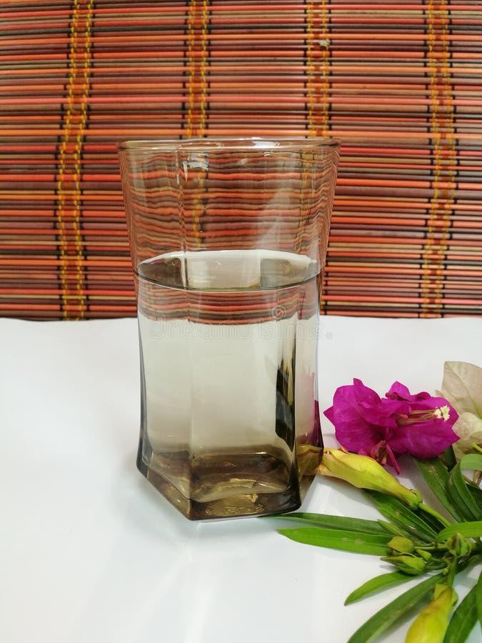 Vidrio de agua de la bebida con las flores fotografía de archivo libre de regalías