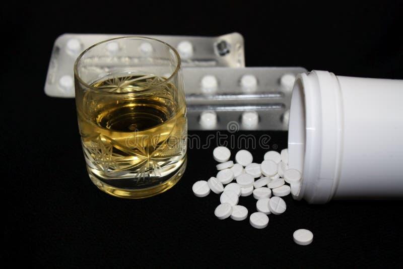 Vidrio de alcohol, de bebida alcohólica y de algunas píldoras blancas foto de archivo