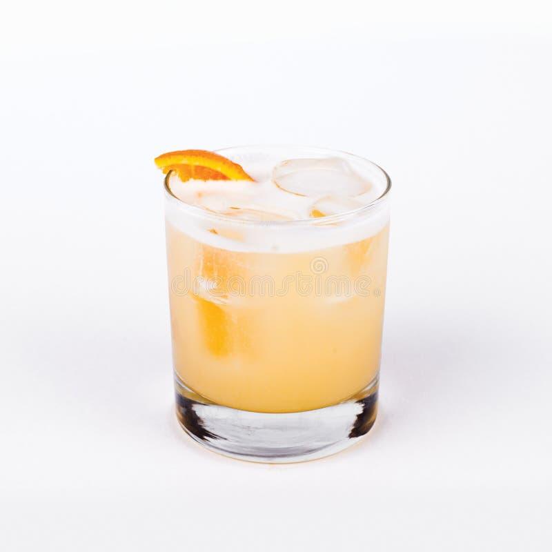 Vidrio de amargo de whisky con la naranja en el fondo blanco imagen de archivo libre de regalías