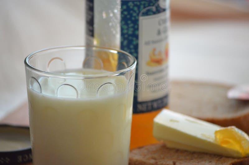 Vidrio de atasco fresco de la leche, de la mantequilla y del albaricoque fotografía de archivo