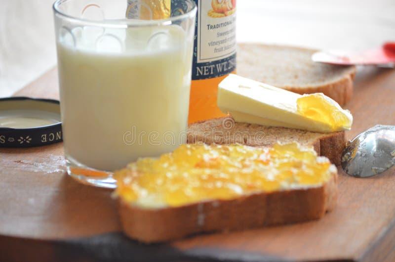 Vidrio de atasco fresco de la leche, de la mantequilla y del albaricoque imágenes de archivo libres de regalías