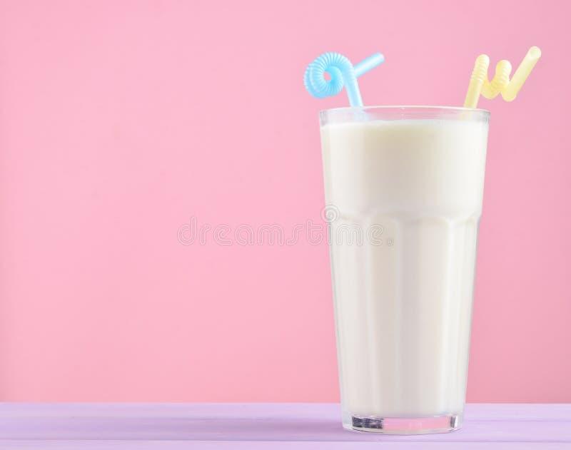 vidrio de batido de leche con una paja en una tabla de madera del color en colores pastel aislada en rosa Copie el espacio fotografía de archivo libre de regalías