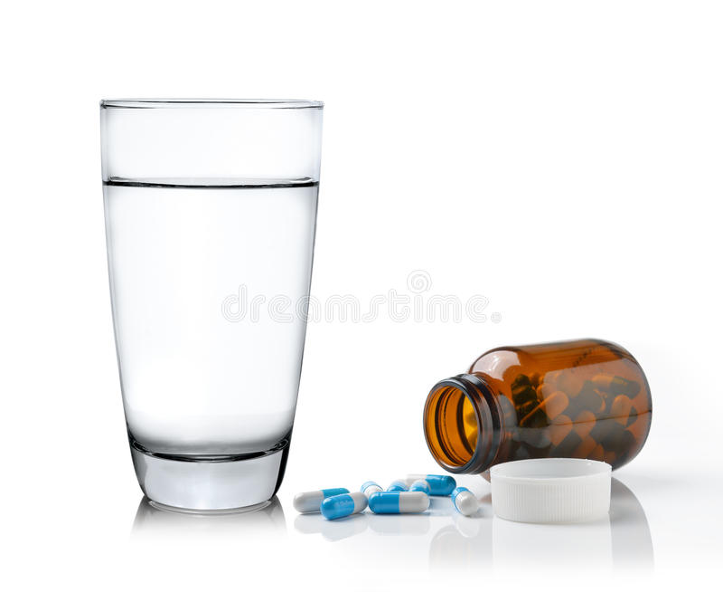 Vidrio de botella y de píldoras de la medicina del agua aisladas en el backg blanco imagenes de archivo