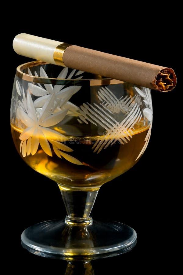 Vidrio de brandy con el cigarrillo fotografía de archivo libre de regalías