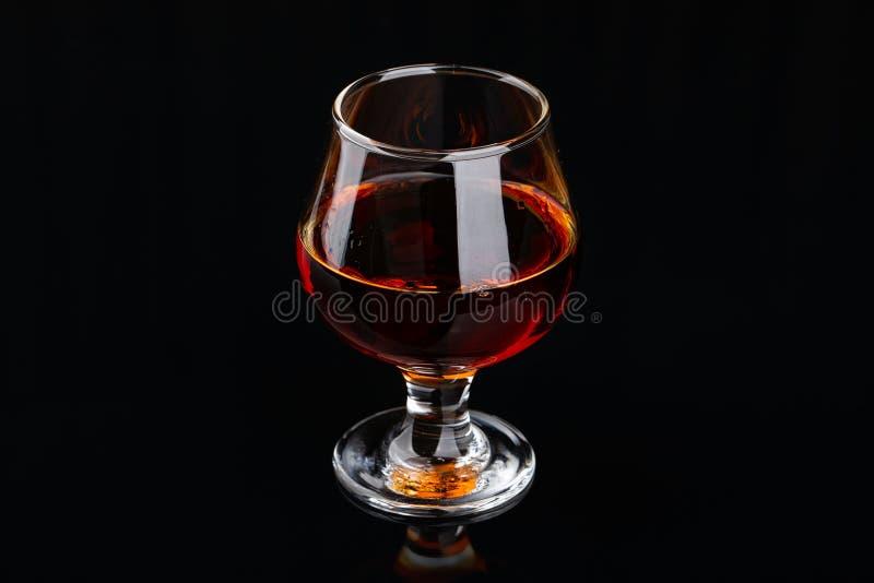 Vidrio de brandy en un fondo negro imagenes de archivo