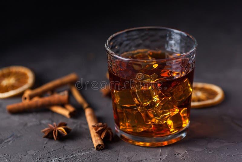 Vidrio de brandy o whisky, especias y decoraciones en fondo oscuro Concepto estacional de los d?as de fiesta imagen de archivo