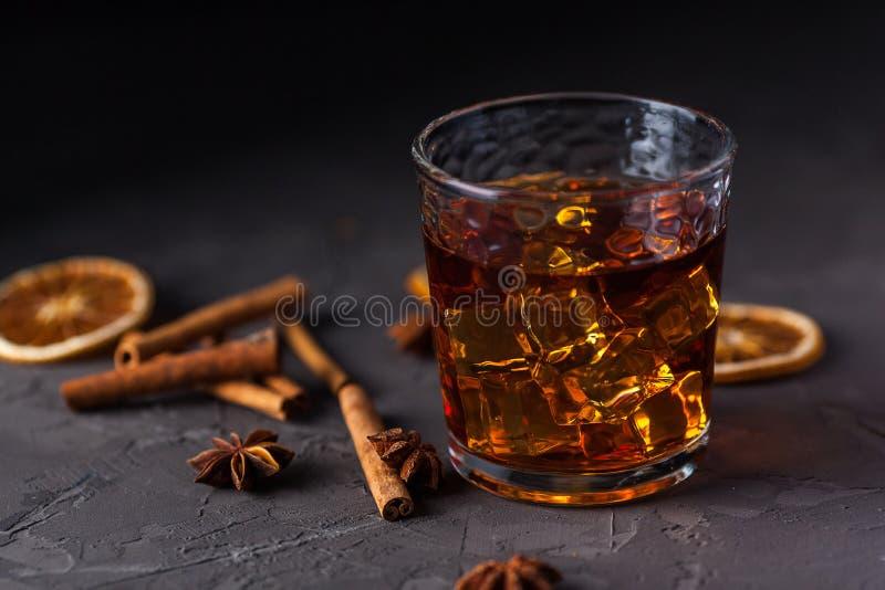 Vidrio de brandy o whisky, especias y decoraciones en fondo oscuro Concepto estacional de los d?as de fiesta fotografía de archivo