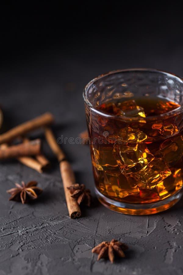 Vidrio de brandy o whisky, especias y decoraciones en fondo oscuro Concepto estacional de los d?as de fiesta imagen de archivo libre de regalías