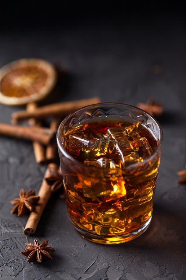 Vidrio de brandy o whisky, especias y decoraciones en fondo oscuro Concepto estacional de los d?as de fiesta imagenes de archivo