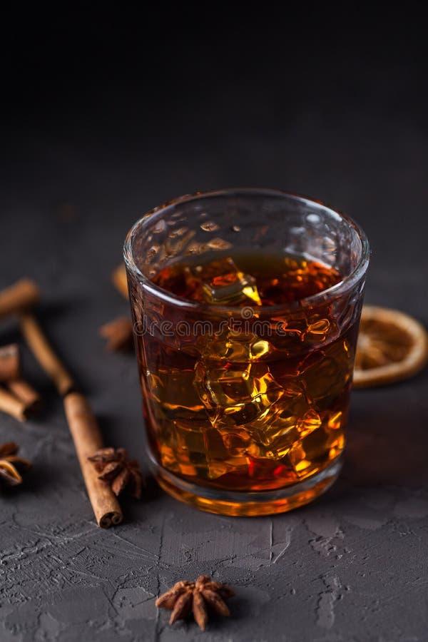 Vidrio de brandy o whisky, especias y decoraciones en fondo oscuro Concepto estacional de los d?as de fiesta imágenes de archivo libres de regalías