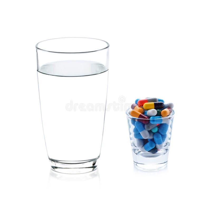 Vidrio de cápsulas del agua y de las píldoras imagenes de archivo