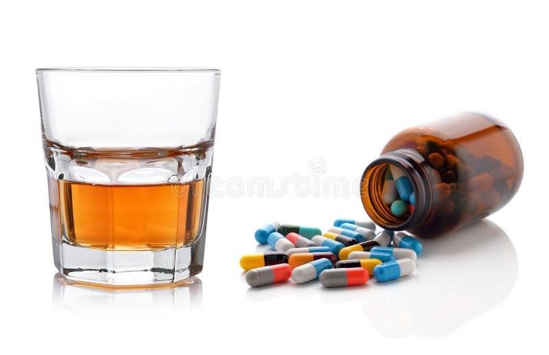 Vidrio de cápsulas del whisky y de las píldoras foto de archivo