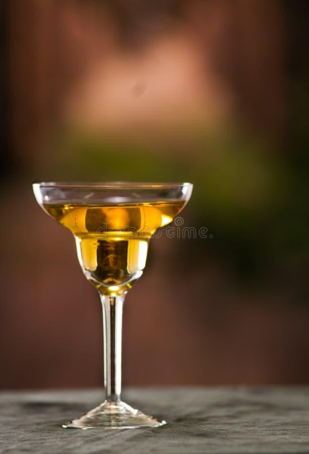 Vidrio de cóctel con clase que se sienta en la superficie gris, líquido amarillo dentro con el fondo urbano borroso fotos de archivo libres de regalías