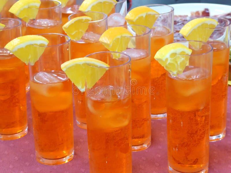 Vidrio de cóctel con el limón y agua tónica y campari fotografía de archivo