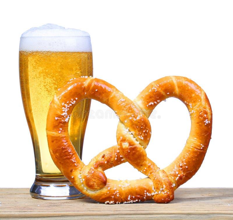Vidrio de cerveza con el pretzel alemán en la tabla de madera. aislado foto de archivo libre de regalías