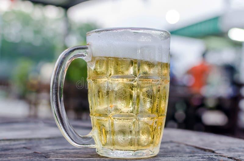 Vidrio de cerveza con escena de la barra en el fondo fotos de archivo