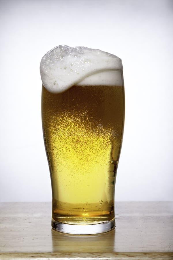 Vidrio de cerveza con la espuma que desborda en blanco imagen de archivo