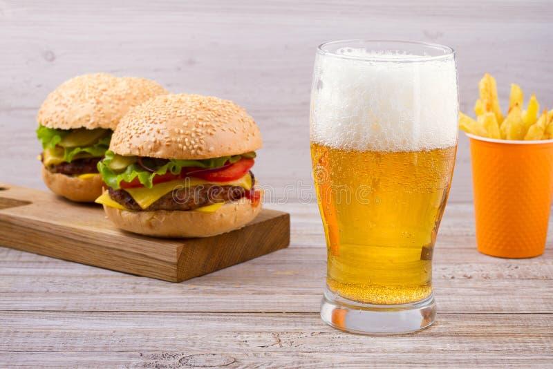Vidrio de cerveza con la hamburguesa y las fritadas en fondo de madera Concepto de la cerveza y de la comida Cerveza inglesa y co imagen de archivo