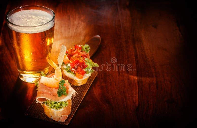 Vidrio de cerveza con tapas deliciosos imagen de archivo libre de regalías