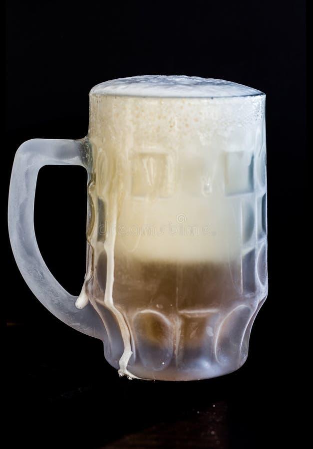 Vidrio de cerveza congelado con espuma en fondo negro imágenes de archivo libres de regalías