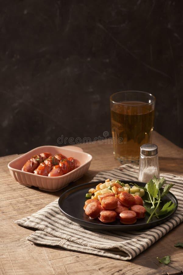 Vidrio de cerveza deliciosa con las salchichas asadas a la parrilla en la tabla de madera foto de archivo libre de regalías