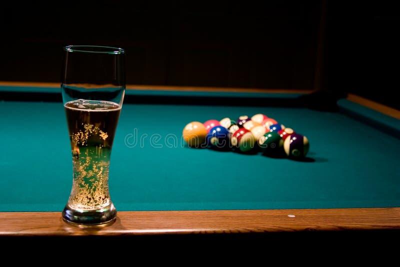 Vidrio de cerveza en el tabl de la piscina fotos de archivo libres de regalías