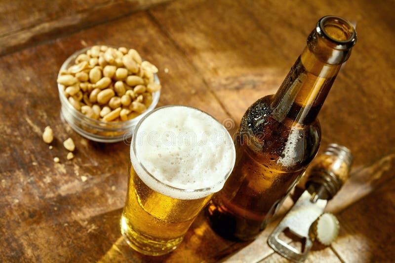 Vidrio de cerveza en la tabla con el abrelatas y los cacahuetes imagen de archivo libre de regalías