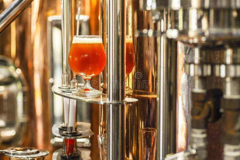 Vidrio de cerveza en una caldera de cobre imagenes de archivo