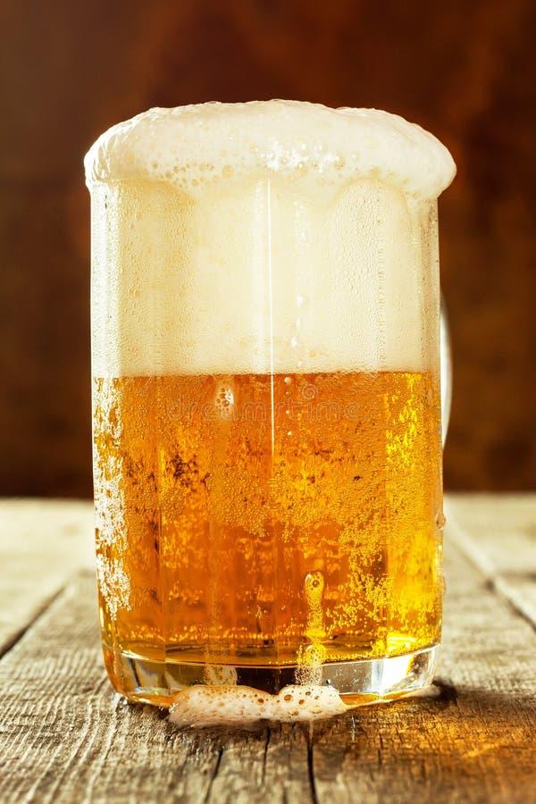 Vidrio de cerveza en una tabla de madera vieja Ventas del alcohol Publicidad de la cerveza imagen de archivo