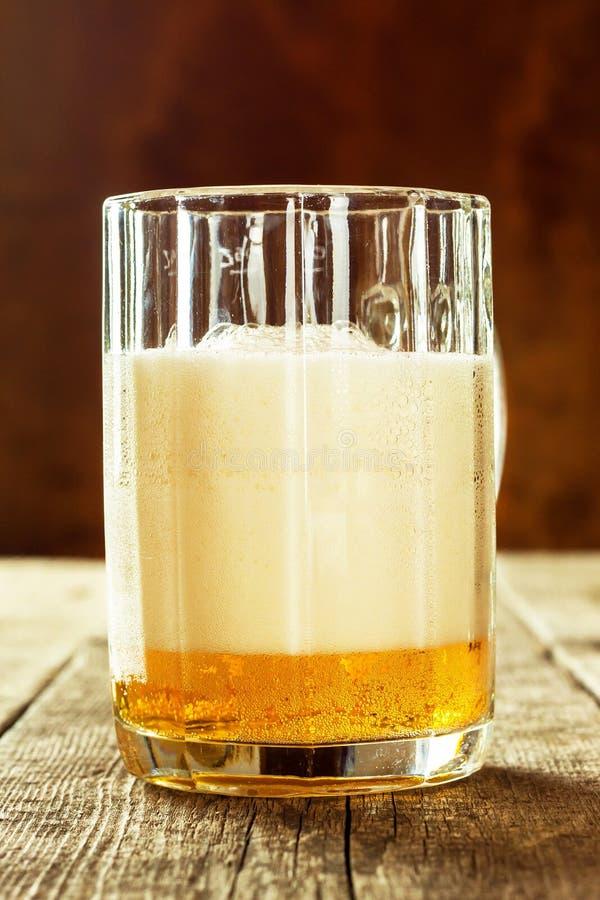 Vidrio de cerveza en una tabla de madera vieja Ventas del alcohol Publicidad de la cerveza fotos de archivo