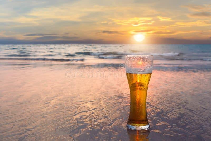 Vidrio de cerveza fría en la orilla de mar en la puesta del sol Relájese en la playa imágenes de archivo libres de regalías