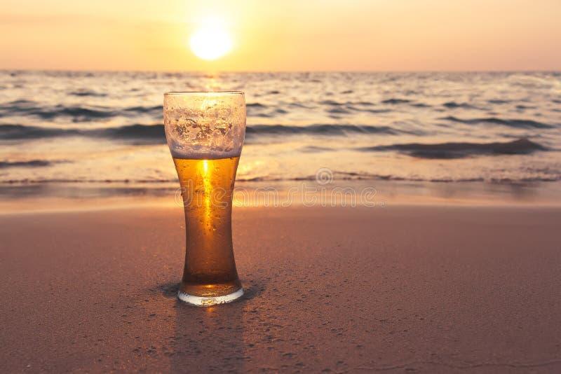 Vidrio de cerveza fría en la orilla de mar en la puesta del sol Relájese en la playa fotos de archivo libres de regalías