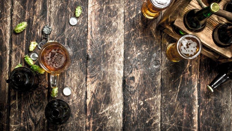vidrio de cerveza fresca con las botellas y el corcho fotos de archivo