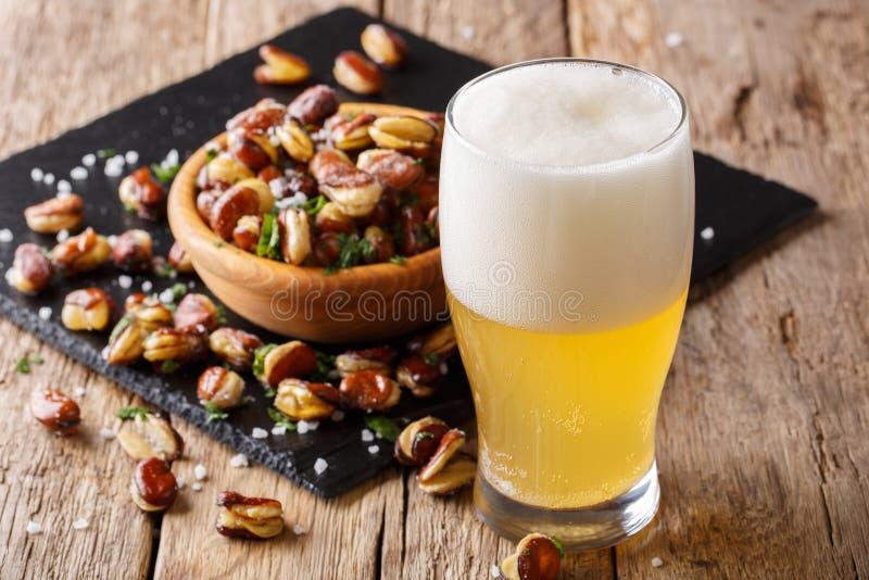 Vidrio de cerveza ligera con el aperitivo del broa salado frito curruscante foto de archivo