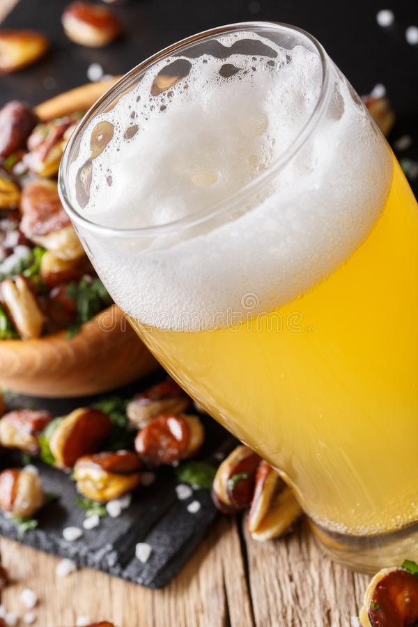 Vidrio de cerveza ligera con un bocado de las habas fritas macras en la etiqueta fotografía de archivo