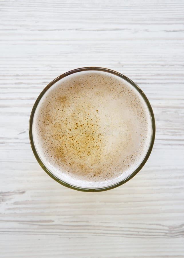 Vidrio de cerveza ligera sobre la superficie de madera blanca, visión superior overhead foto de archivo