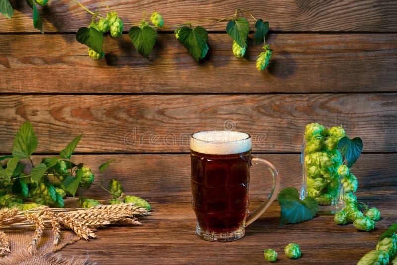Vidrio de cerveza oscuro de cerveza dorada, cerveza inglesa marrón en la tabla de madera en barra o pub foto de archivo