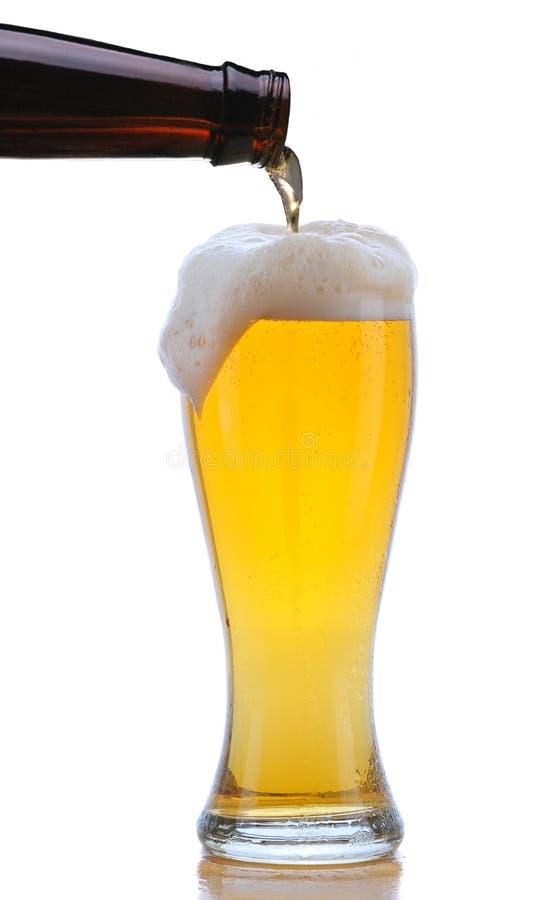 Vidrio de cerveza que es vertida imagen de archivo libre de regalías