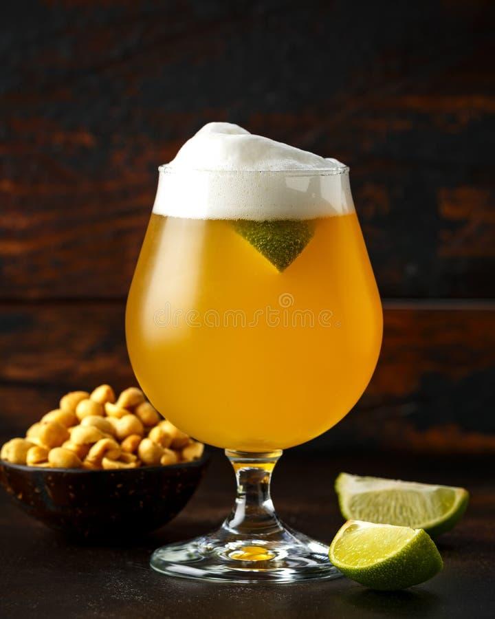 Vidrio de cerveza sin filtro enfriada con las cuñas de la cal y los cacahuetes salados en fondo de madera foto de archivo libre de regalías