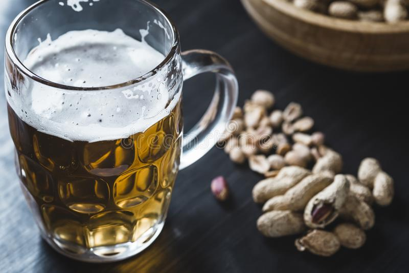 Vidrio de cerveza y de cacahuetes en el fondo de madera fotos de archivo