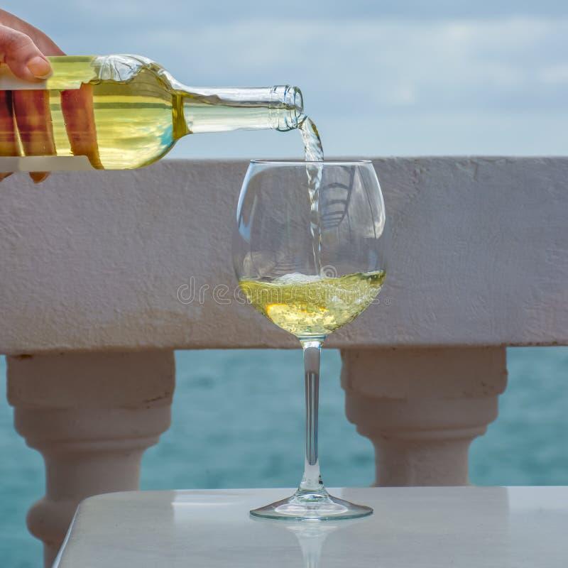 Vidrio de colada del camarero de vino blanco en terraza al aire libre con el mar v imagenes de archivo