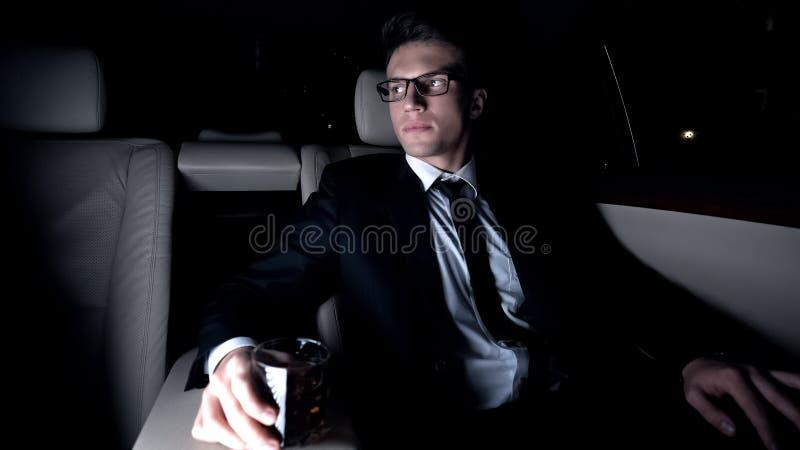 Vidrio de consumición del millonario de brandy de la élite en el asiento trasero del coche, viaje de negocios fotografía de archivo