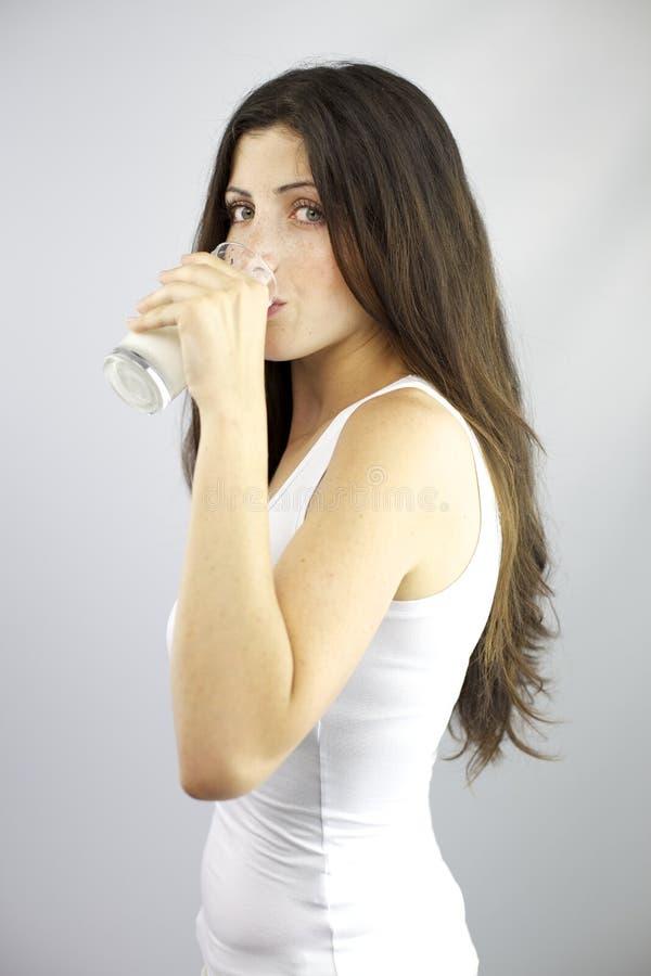 Vidrio de consumición hermoso de la mujer de leche imagen de archivo libre de regalías