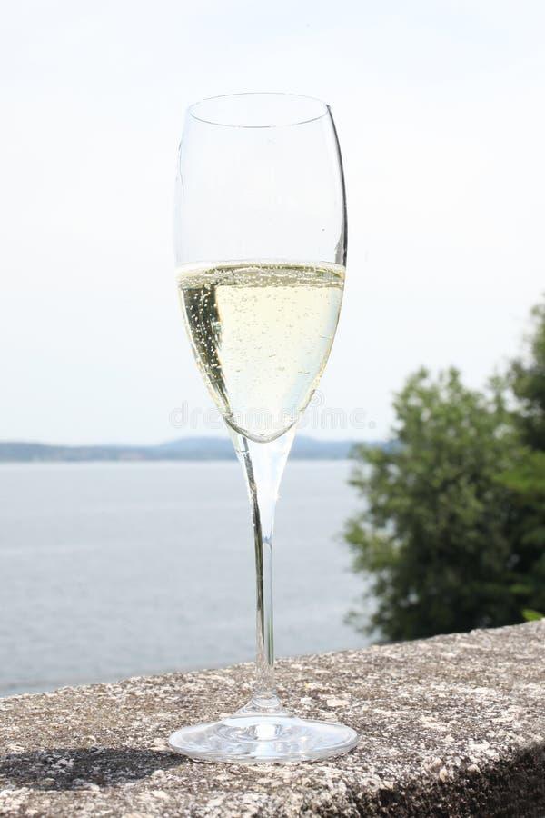 Vidrio de flauta con el vino del champán en una barandilla de piedra foto de archivo